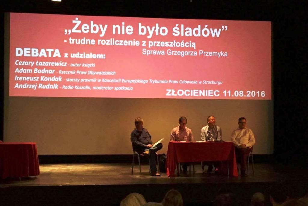 Zdjęcie: paneliści siedzą pod tytułem panelu na czerwonym tle