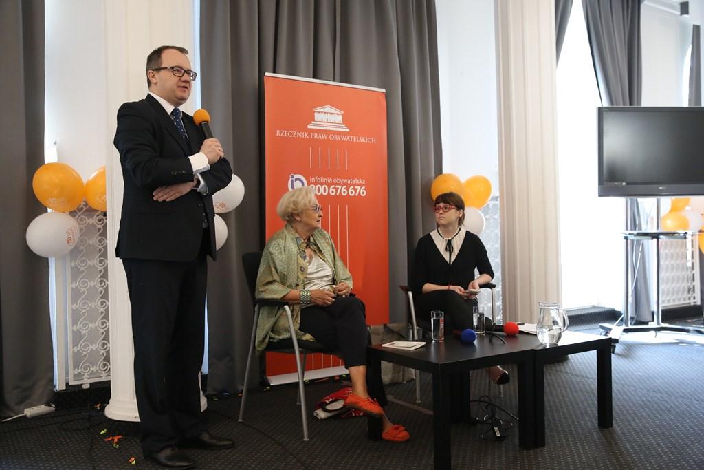 zdjęcie: mężczyzna w garniturze stoi i mówi do mikrofonu, obok niego na krzesłach siedzą dwie kobiety