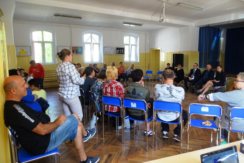 Ludzie na spotkaniu siedzą w kręgu. Kobieta w jasnej koszuli stoi i mówi