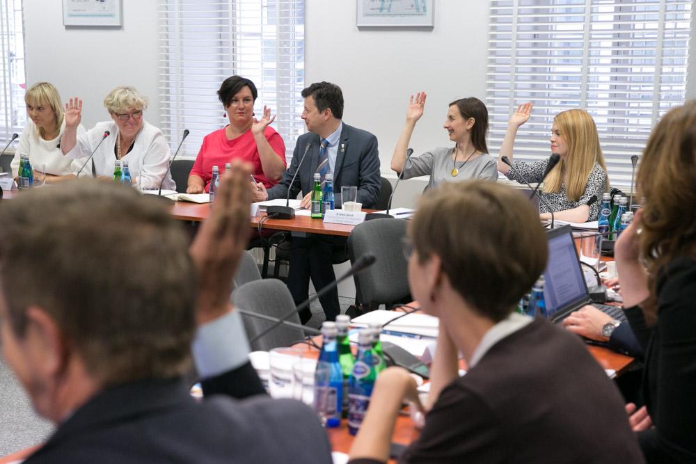zdjęcie: ludzie siedzą przy stołach ustawionych w kształcie litery U, niektórzy z nich podnoszą rękę do góry w geście głosowania