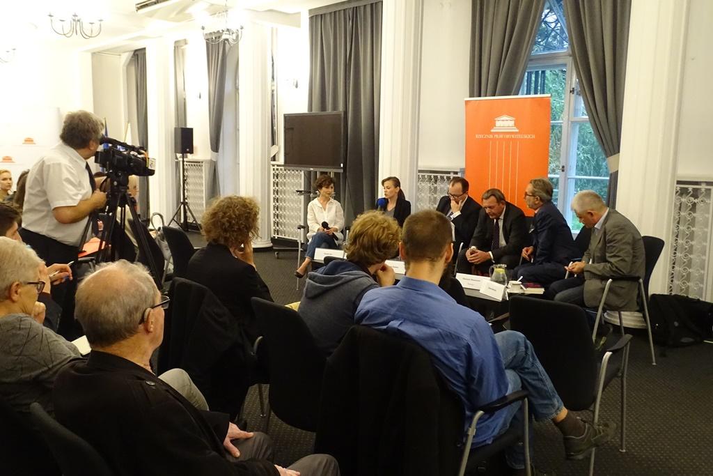 Ludzie na sali, czworo dyskutantów i tłumacz