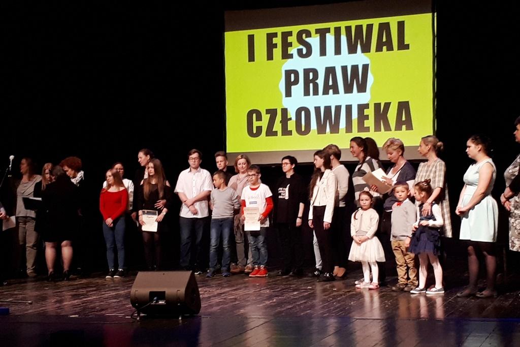 zdjęcie: na scenie stoi kilkadzisiąt młodych osób za nimi napis: I Festiwal Praw Człowieka