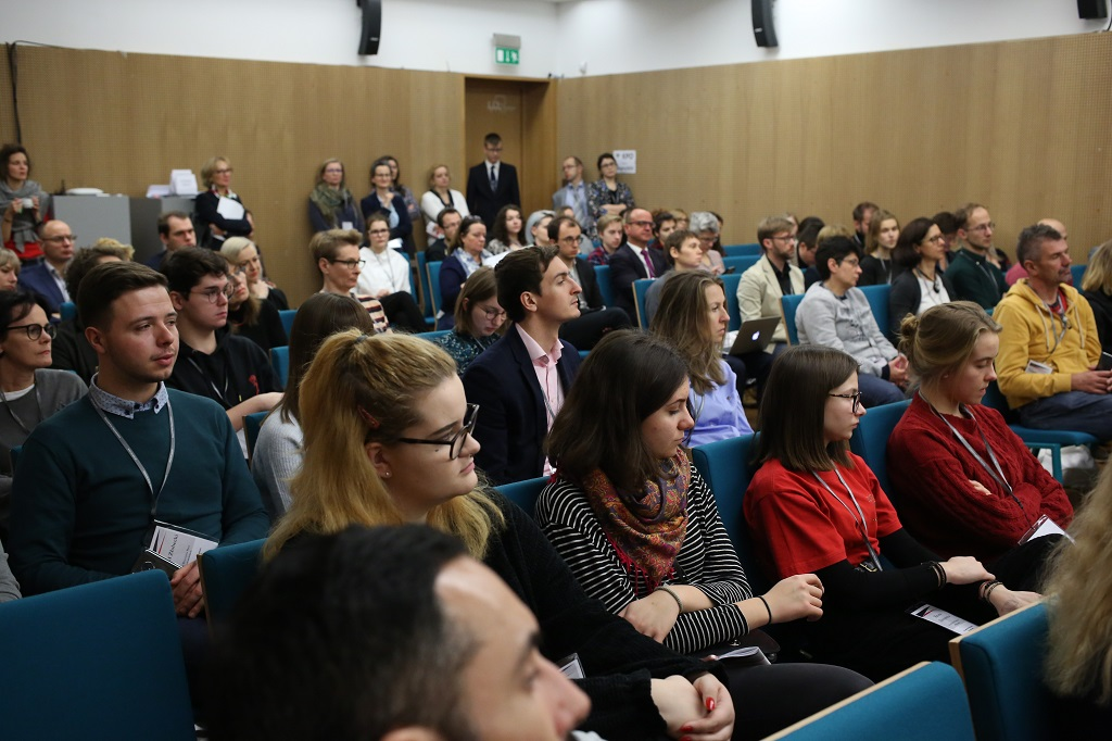 Pełna sala konferencyjna, zielone krzesla