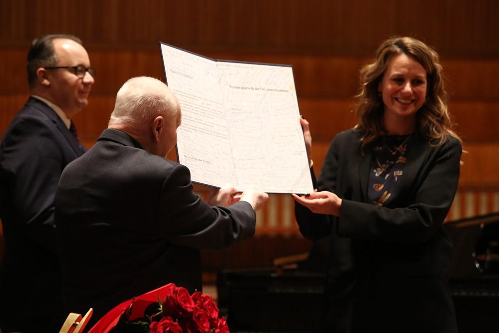 Trzy osoby trzymają dokument
