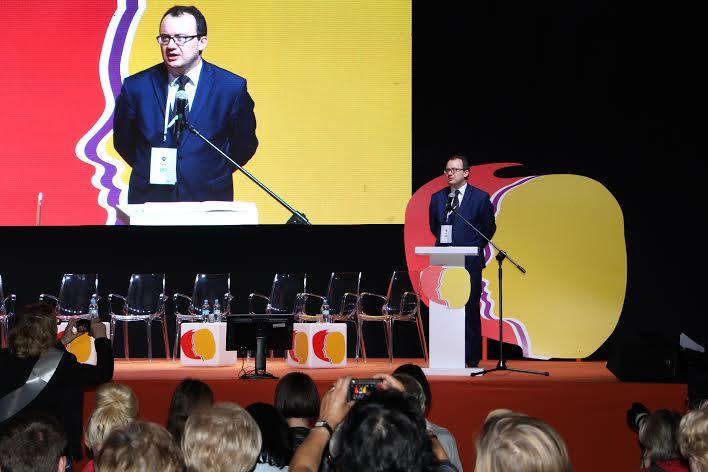 Zdjęcie: mężczyzna przemawia, jego postać powiększona na ekranie z tyłu