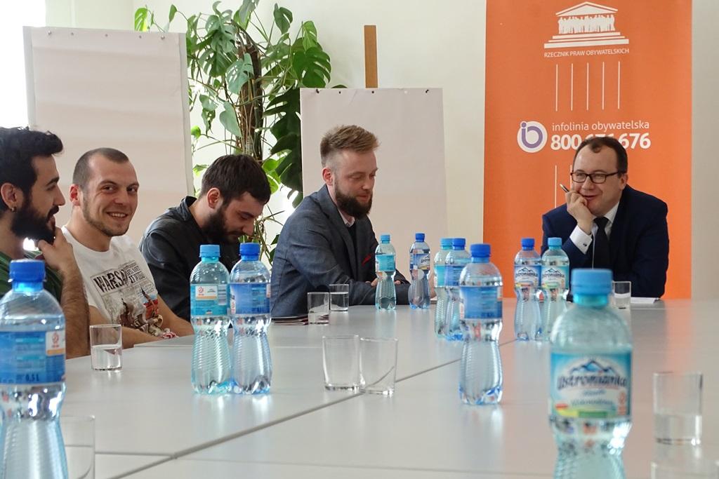 Zdjęcie: grupa ludzi przy stole. Widac butelki z woda mineralną