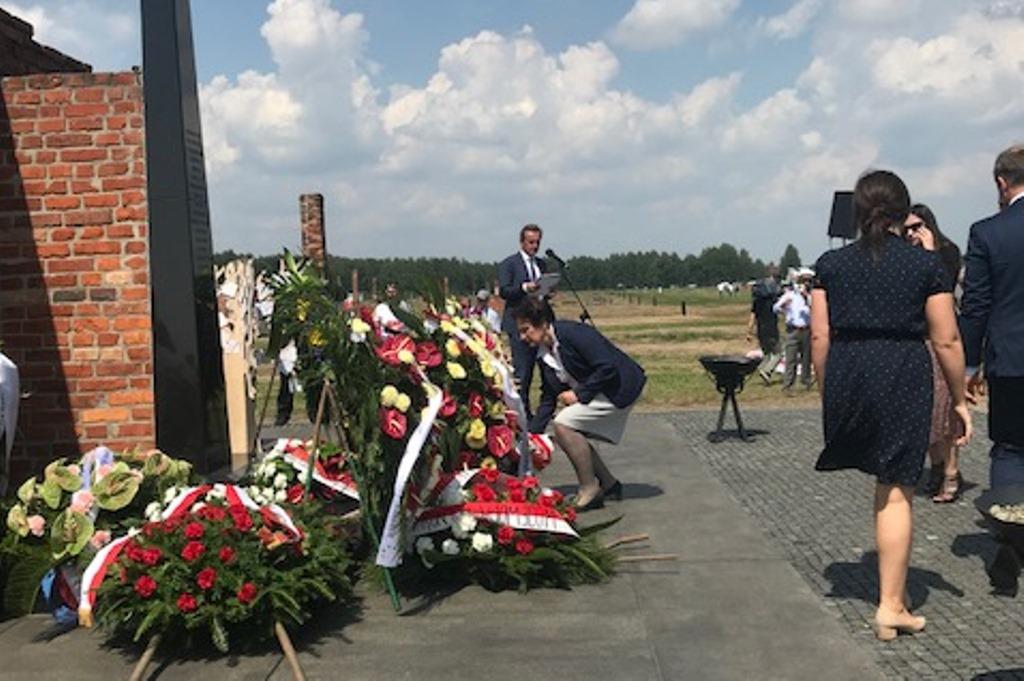 Kobieta składa wieniec przed pomnikiem
