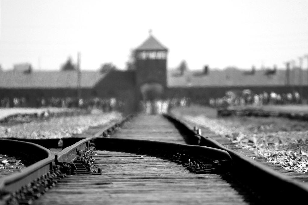 Czarno-białe zdjęcie bramy Auschwitz i rozjazdu kolejowego