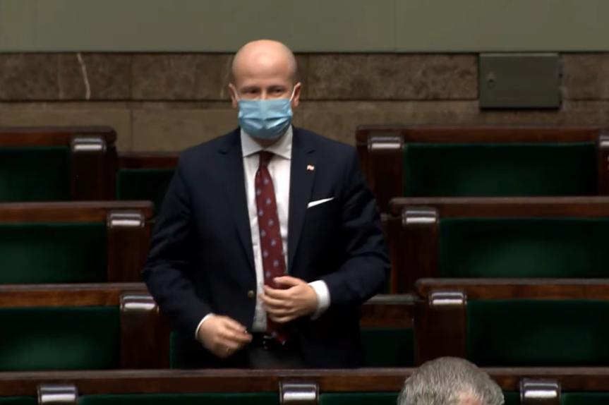 Osoba stoi w sali plenarnej Sejmu