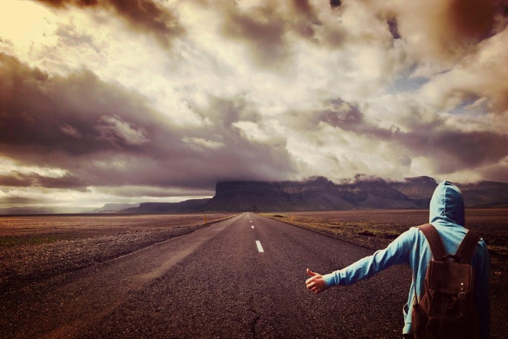 Młody autostopowicz na zupełnie pustej drodze czeka, aż ktoś mu pomoże