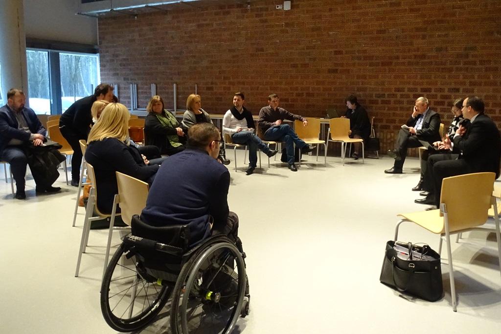 Zdjęcie: grupa ludzi w tym osoba na wózku rozmawia siedząc w kręgu w nowoczesnym wnętrzu