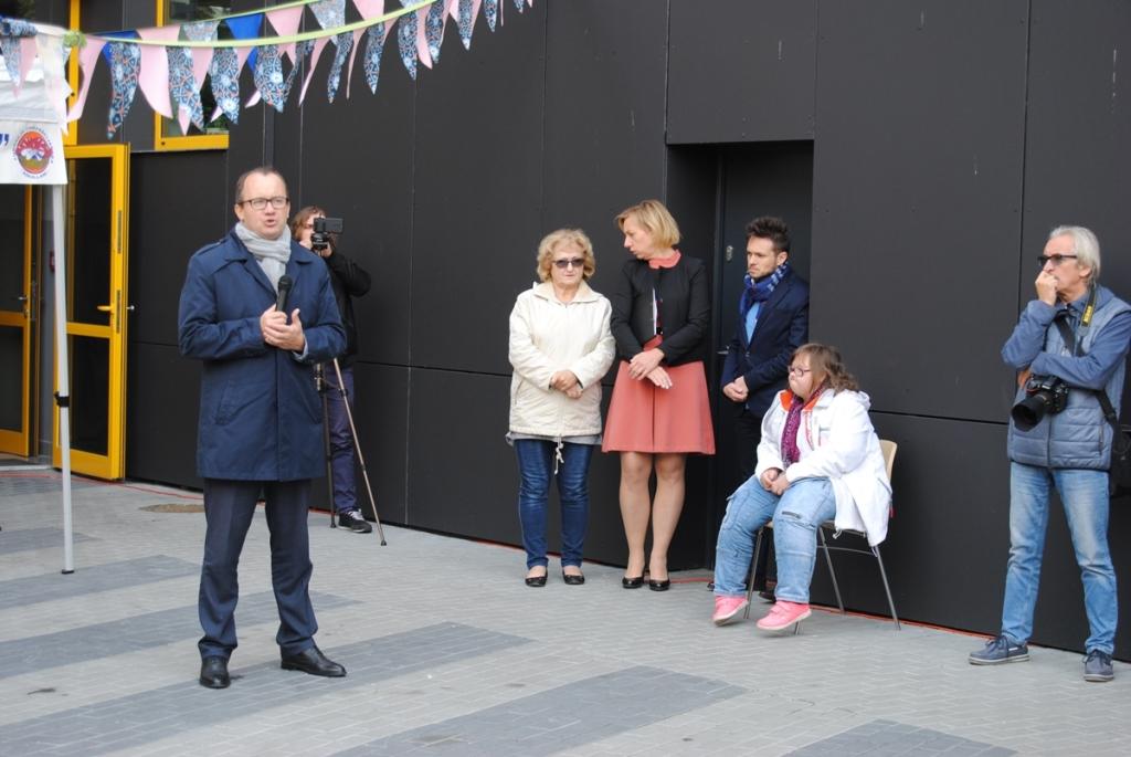 Mężczyzna w kurtce mówi do mikrofonu. Na krześle siedzi dziewczynka z niepełnosprawnością