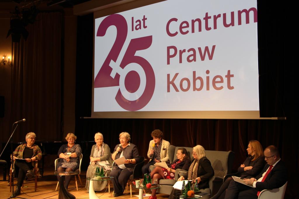 Paneliści siedzą na scenie