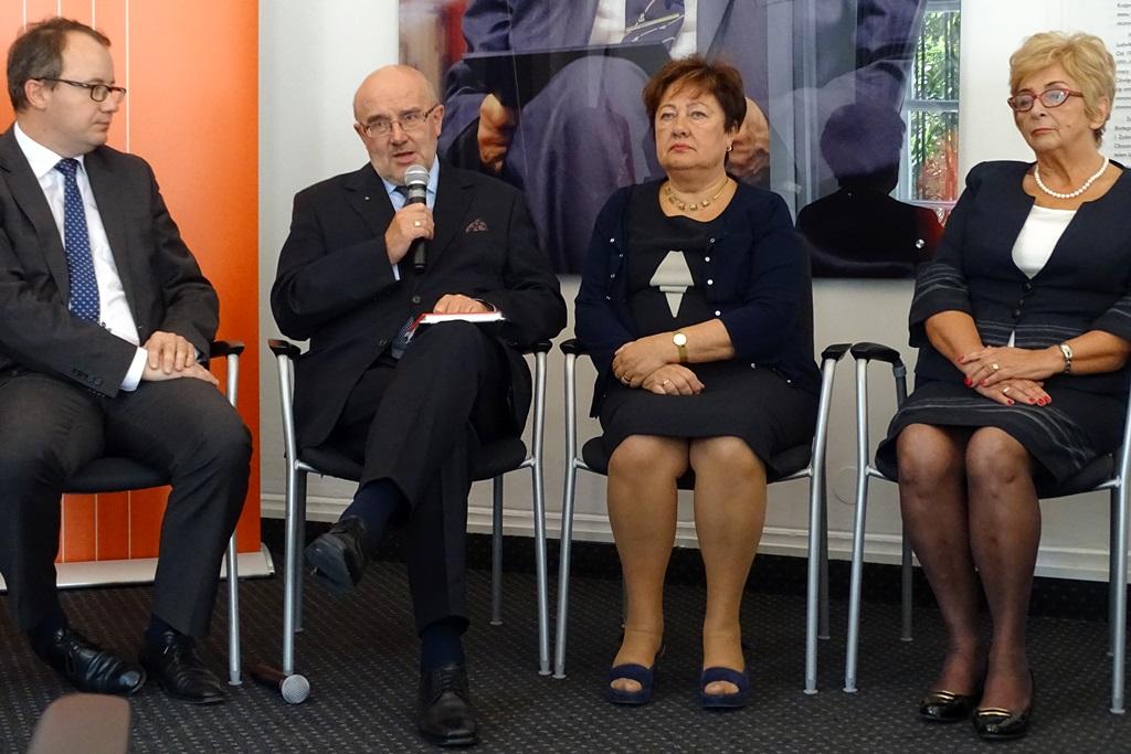zdjęcie: dwaj mężczyźni i dwie kobiety siedzą na krzesłach, mężczyzna drugi od lewej mówi do mikrofonu