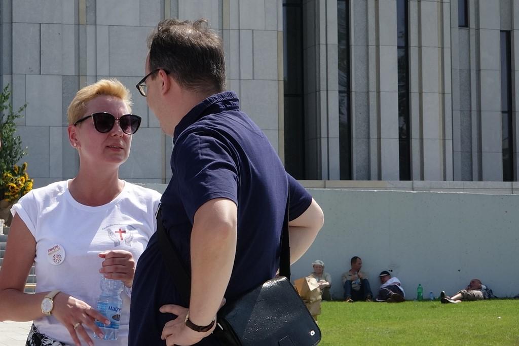 Zdjęcie: mężczyzna i kobieta rozmawiają przed nowoczesną budowlą