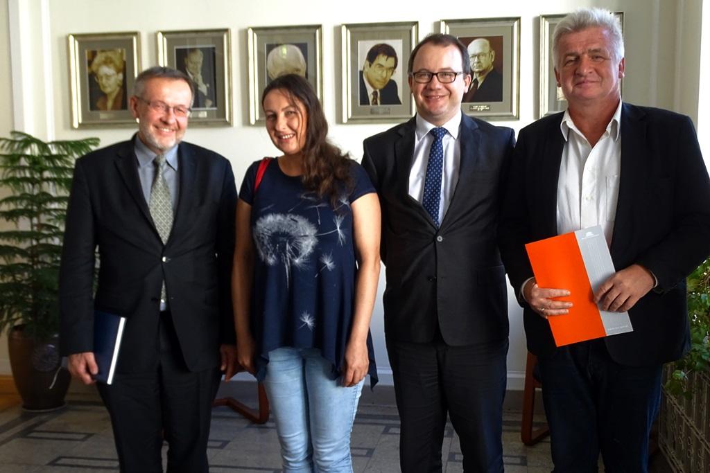 zdjęcie: na zdjęciu stoją trzej mężczyźni i jedna kobieta, mężczyzna po lewej trzyma pomarańczową teczkę