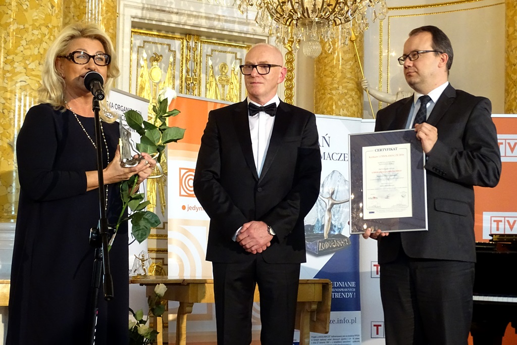 zdjęcie: do mitrofonu mówi blondynka w czarnej sukience, dwaj mężczyźni stoją obok, jeden z nich trzyma oprawiony dyplom