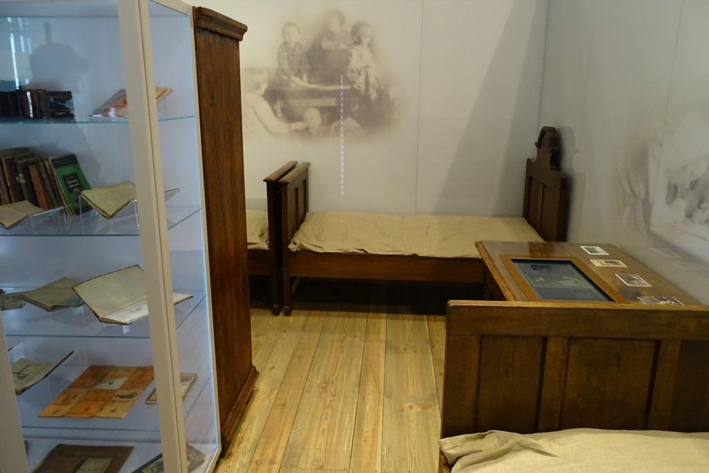 Zdjęcie: sala muzealna z prostymi sprzętami domowymi: łóżkiem i szafą