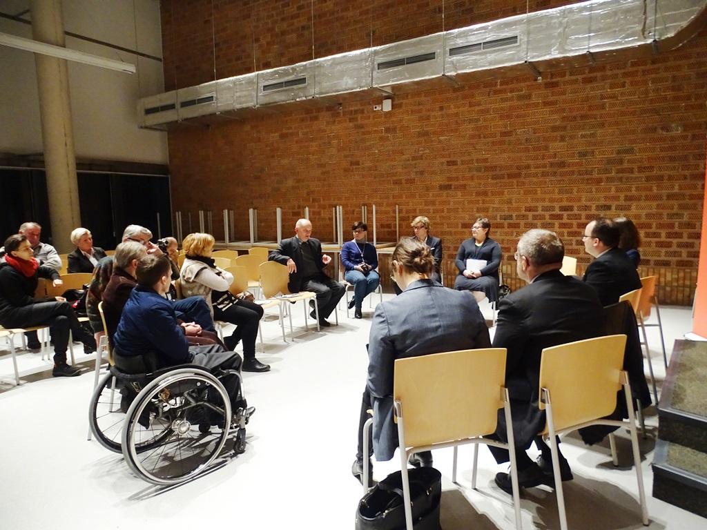 Zdjęcie: uczestnicy spotkania siedzą w kręgu. Na pierwszym planie osoba na wózku inwalidzkim