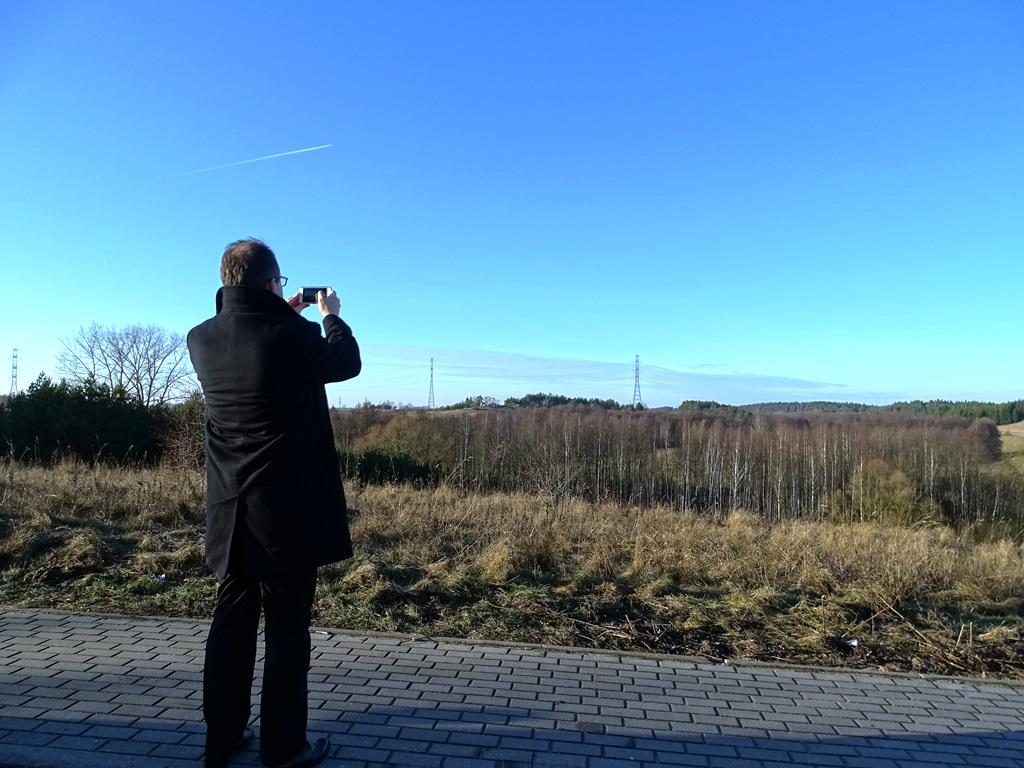 Zdjęcie: Adam Bodnar stoi t tyłem z aparatem, na horyzoncie linia przesyłowa