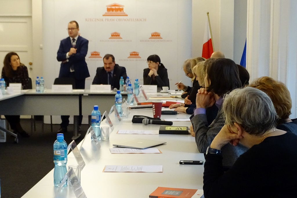 zdjęcie: po prawej stronie widać osoby siedzące przy stole, które patrzą na mężczyznę stojącego przed nimi