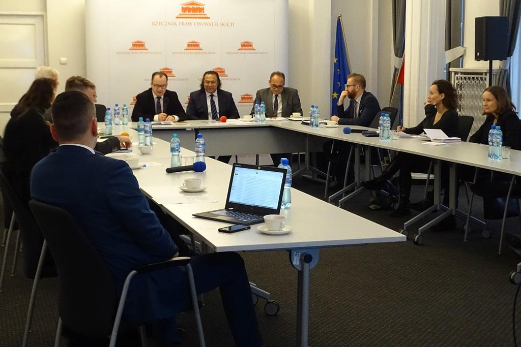 zdjęcie: kilkanaście osób siedzi na sali przy białych stołach