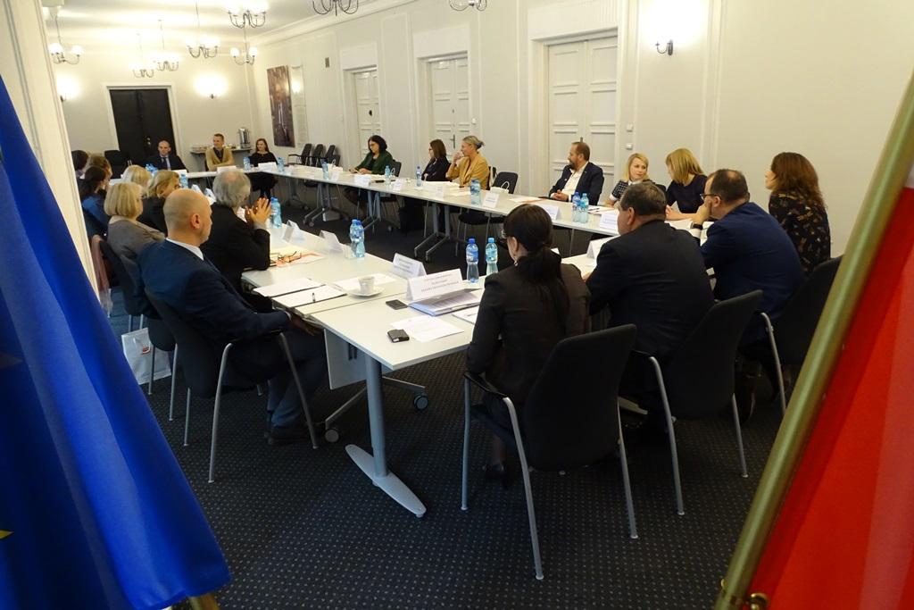 zdjęcie: zza flag widać kilkanaście osób siedzących przy stołach