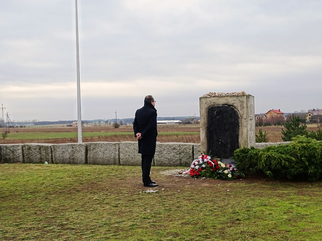 Mężczyzna przed pomnikiem, przed którym leżą kwiaty