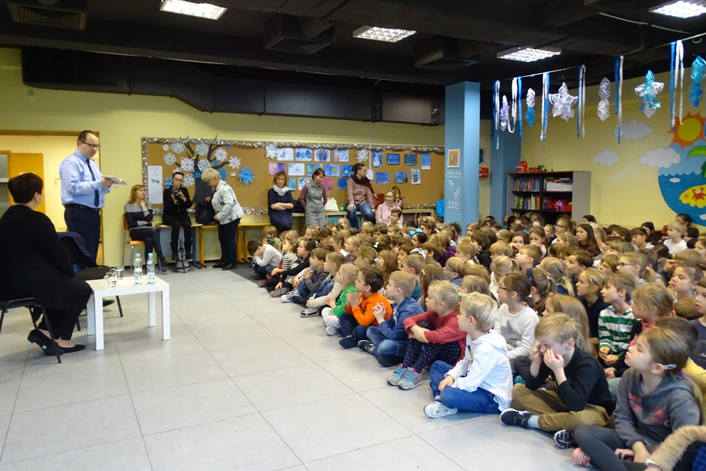 zdjęcie: na podłodze siedzi kilkudziesięciu uczniów, przed nimi stoi mężczyzna w niebieskiej koszuli