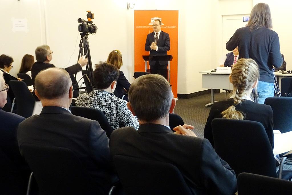 zdjęcie: na pierwszym planie widać grupę siedzących osób w oddali stoi mężczyzna przy mównicy
