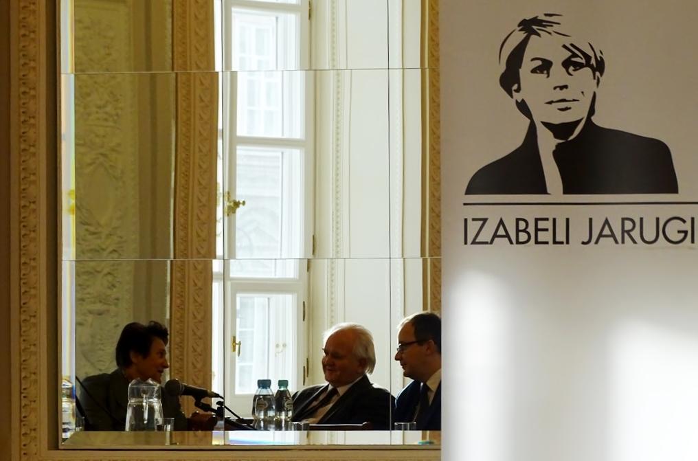 zdjęcie: po prawej stronie widać baner z podobizną kobiety po lewo jest lustro, w który widać dwóch mężczyzn i kobietę