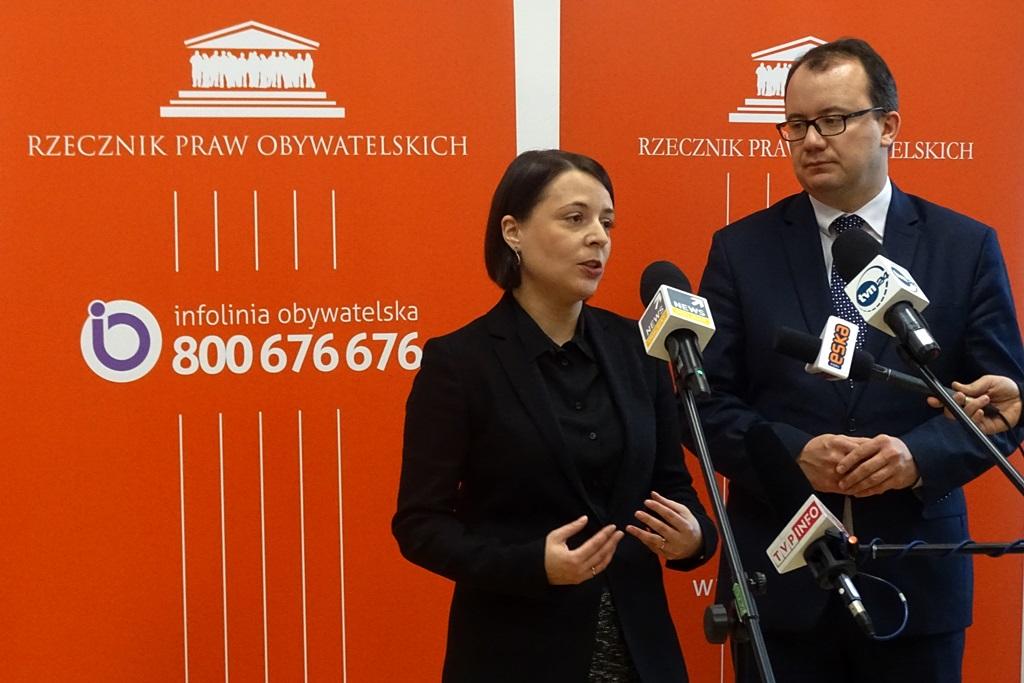 zdjęcie: na pomarańczowym tle widać kobiete w czarnym żakiecie i mężczyznę w garniturze, przed nimi stoją mikrofony