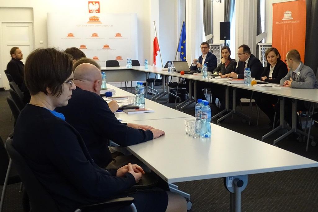zdjęcie: kilka osób siedzi przy białych stołach naprzeciw siebie