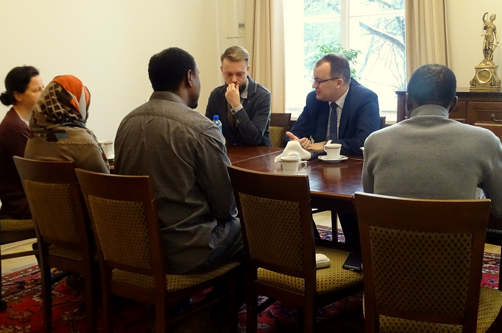 zdjęcie: przy stole tyłem siedzą cztery osoby, po drugiej stronie stołu są dwaj mężczyźni