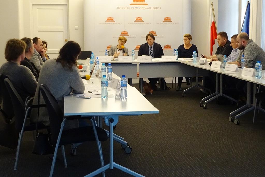 zdjęcie: kilka osób siedzi przy białych stołach