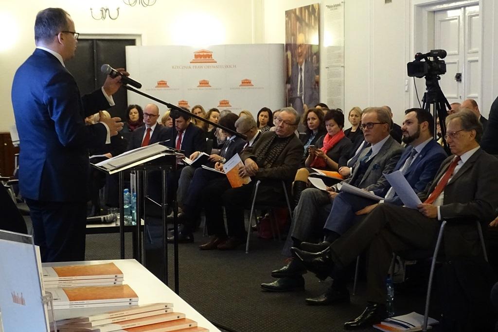zdjęcie: po lewej stronie tyłem stoi mężczyzna przed nimi na krzesłach ustawionych w półkole siedzi kilkadziesiąt osób
