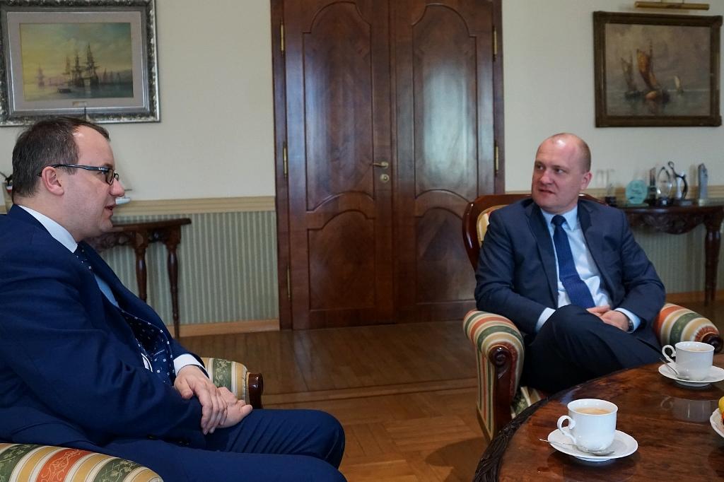 Dwaj mężczyźni rozmawiają siedząc w fotelach