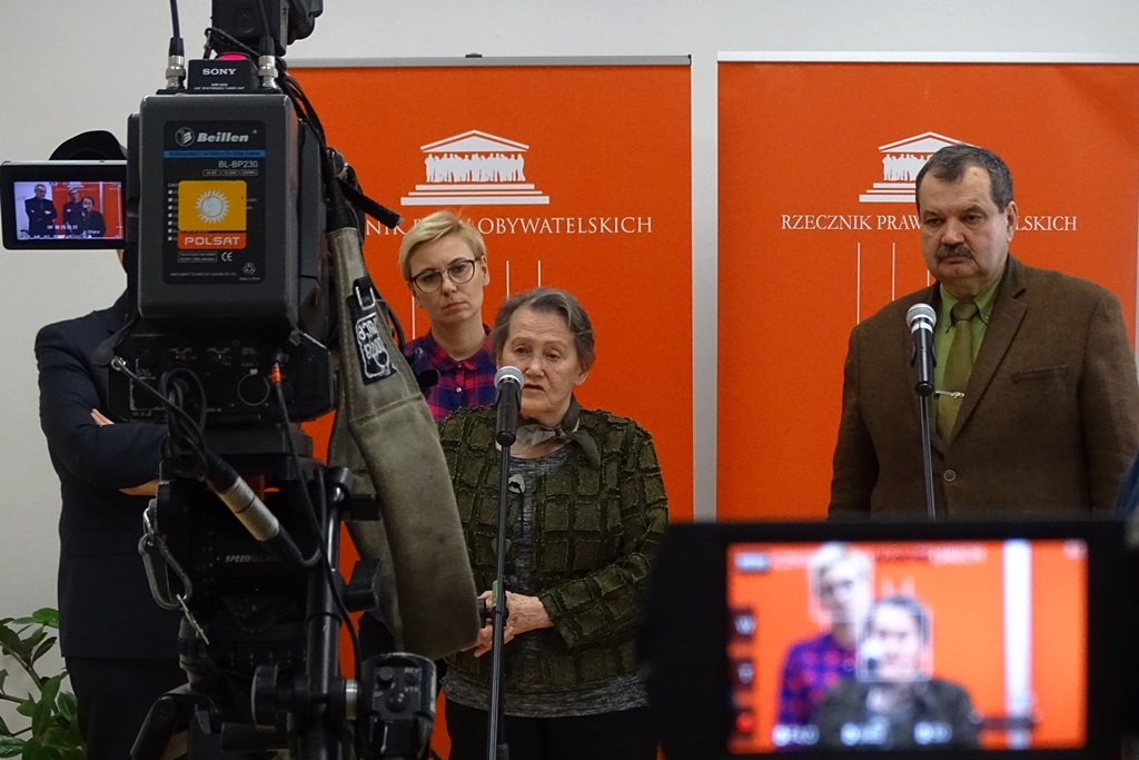 zdjęcie: po lewej stronie widać kamerę, po środku na pomarańczowym tle stoją dwie kobiety, po prawej stronie stoi mężczyzna w brązowej marynarce