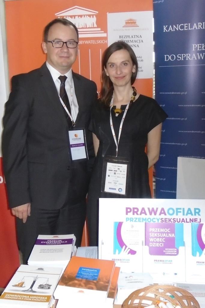 widać: stojących obok siebie rzecznika dr. Adama Bodnara i rzeczniczkę Sylwię Spurek, w tle roll up z białymi napisami na pomarańczowym tle i logo Rzecznika Praw Obywatelskich