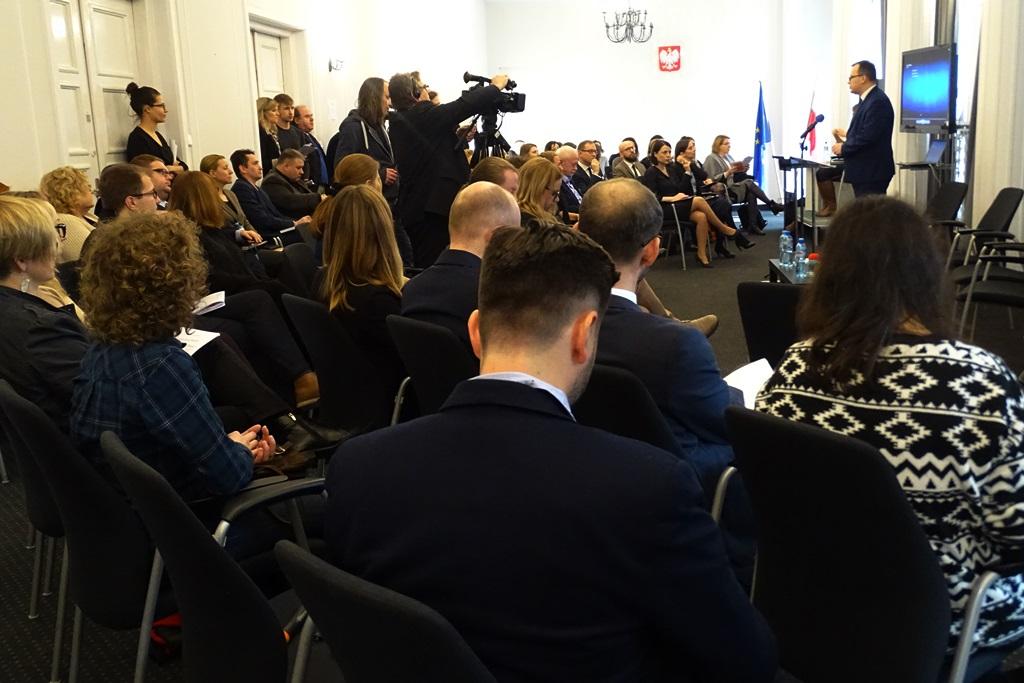 zdjęcie: kilkadziesiądt osób siedzi na sali po prawej stronie widać mężczyznę w garniturze, który przemawia