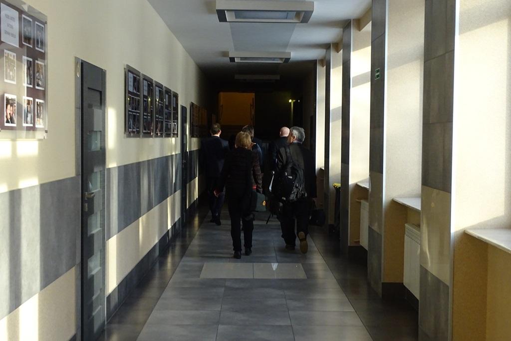 zdjęcie: tyłem widać kilka osób idących korytarzem
