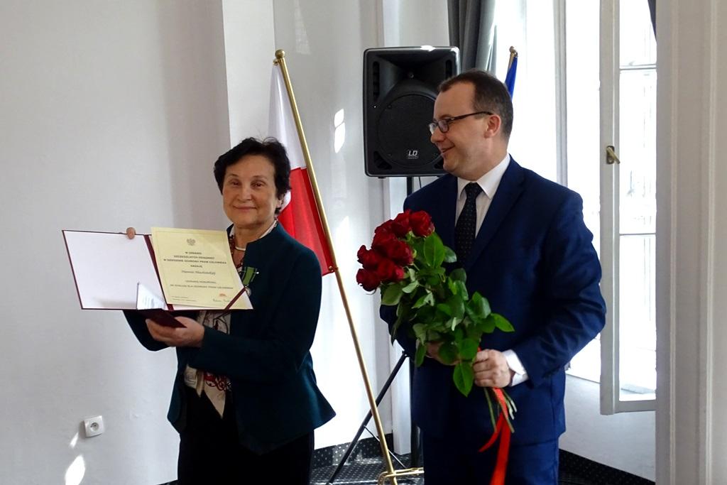 Kobieta pokazuje dyplom, obok  mężczyzna z kwiatami