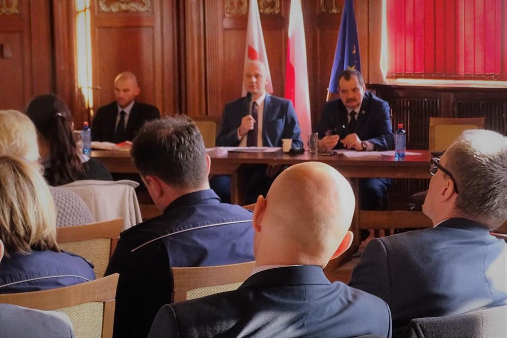 zdjęcie: za stołem siedzi trzech mężczyzn, przed nimi siedzi kilka osób