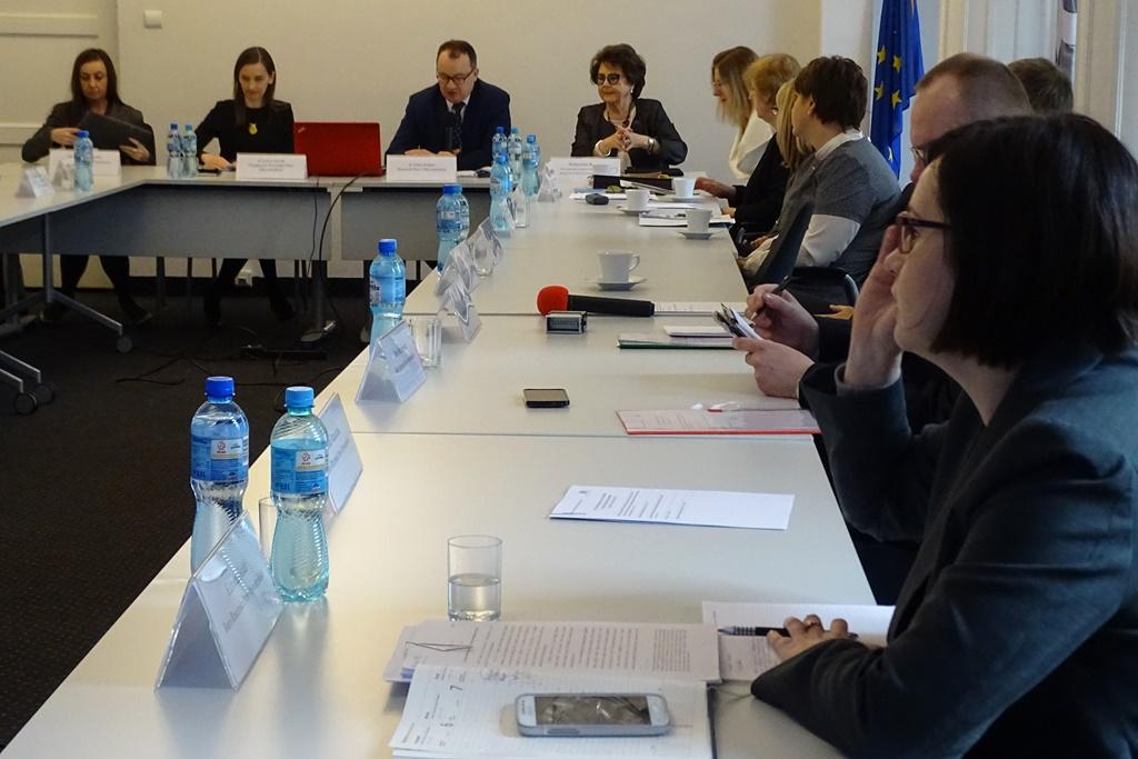 zdjęcie: przy białych stołach siedzi kilkanaście osób