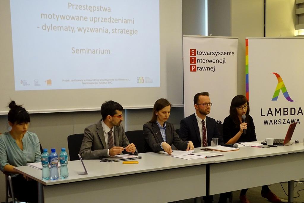 zdjęcie: dwaj mężczyźni i trzy kobiety siedzą przy stole, jedna z kobiet mówi do mikrofonu