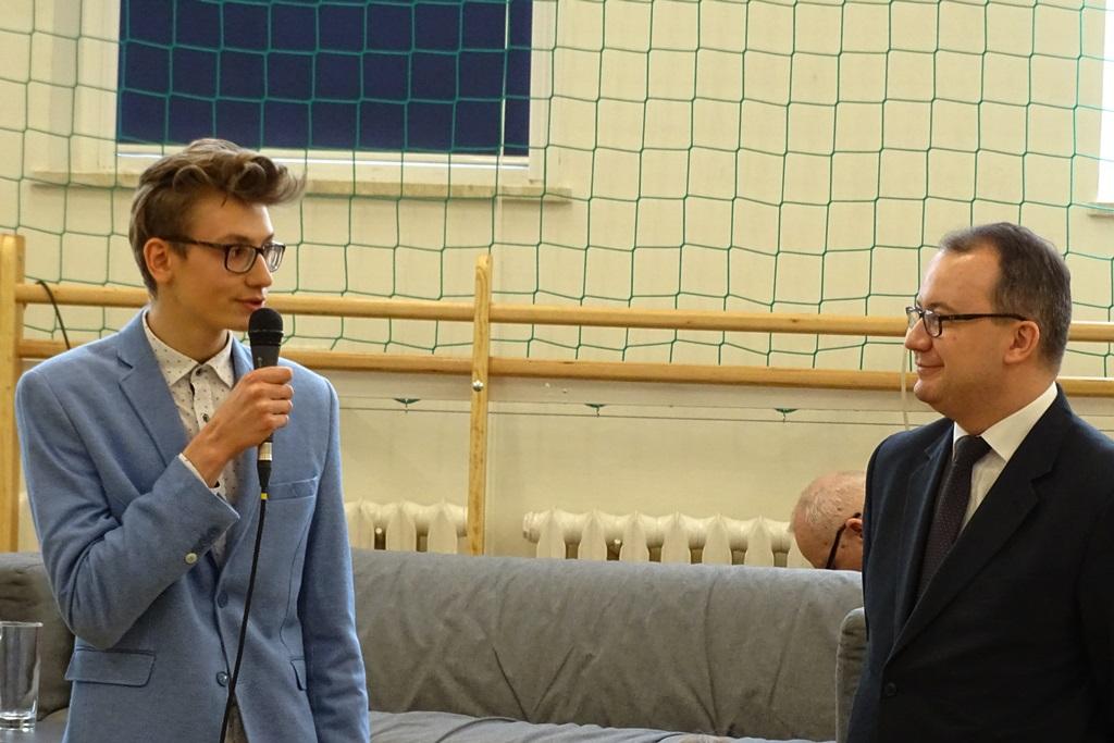 zdjęcie: po lewej stronie stoi młody chłopak w błękitnej marynarce, który mówi do mikrofonu, po prawej tronie stoi mężczyzna w garniturze