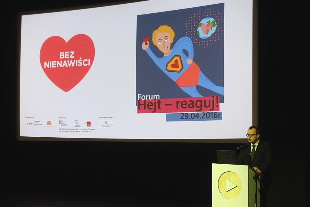zdjęcie: tłem jest grafika wyświetlana na monitorze znajduje się na niej serce z napisem Bez Nienawiści, obok jest postać superbohatera z serdem w dłoni, na pierwszym planie, przy pulpicie stoi mężczyzna w garniturze