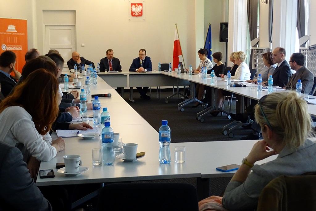 zdjęcie: kilkanaście osób siedzi przy białych stołach ustawionych w prostokąt