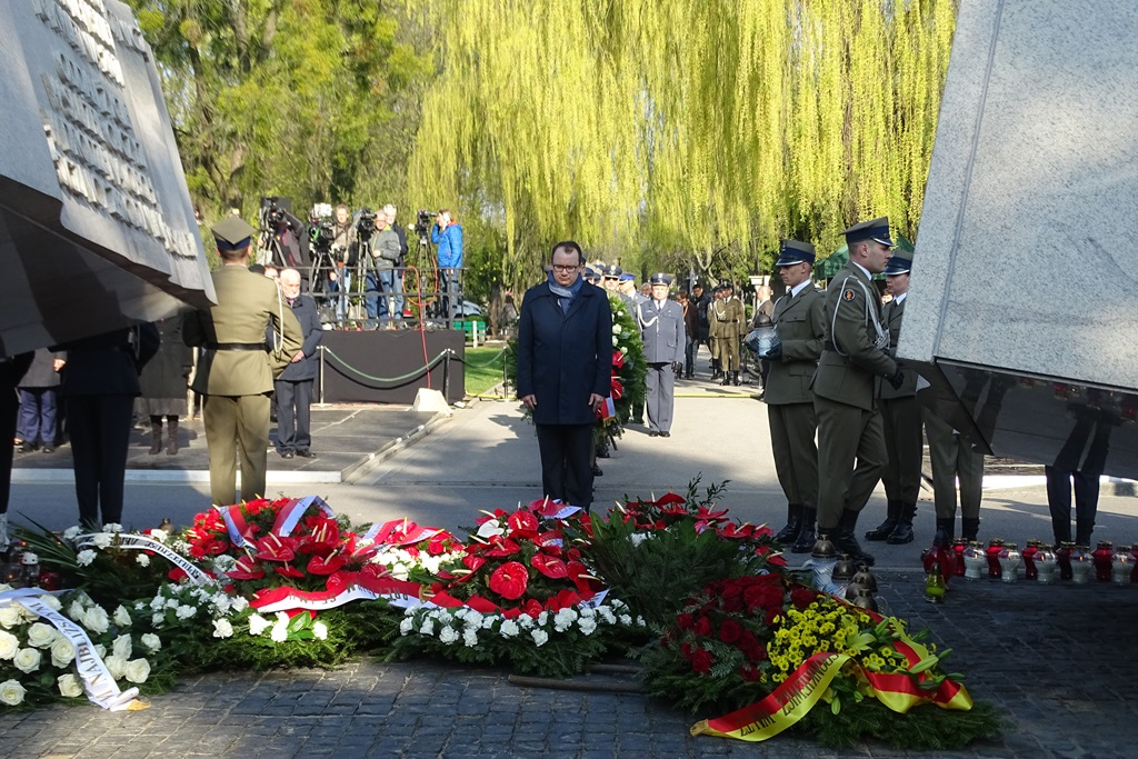 zdjęcie: po bokach widać fragmenty pomnika smoleńskiego, na wprost stoi mężczyzna, który pochyla głowę, przed nim leżą wieńce z kwiatami