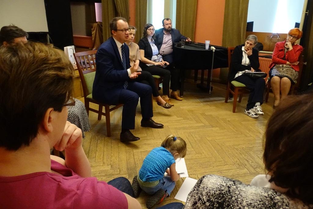 Ludzie siedzą, na podłodze bawi się dziecko